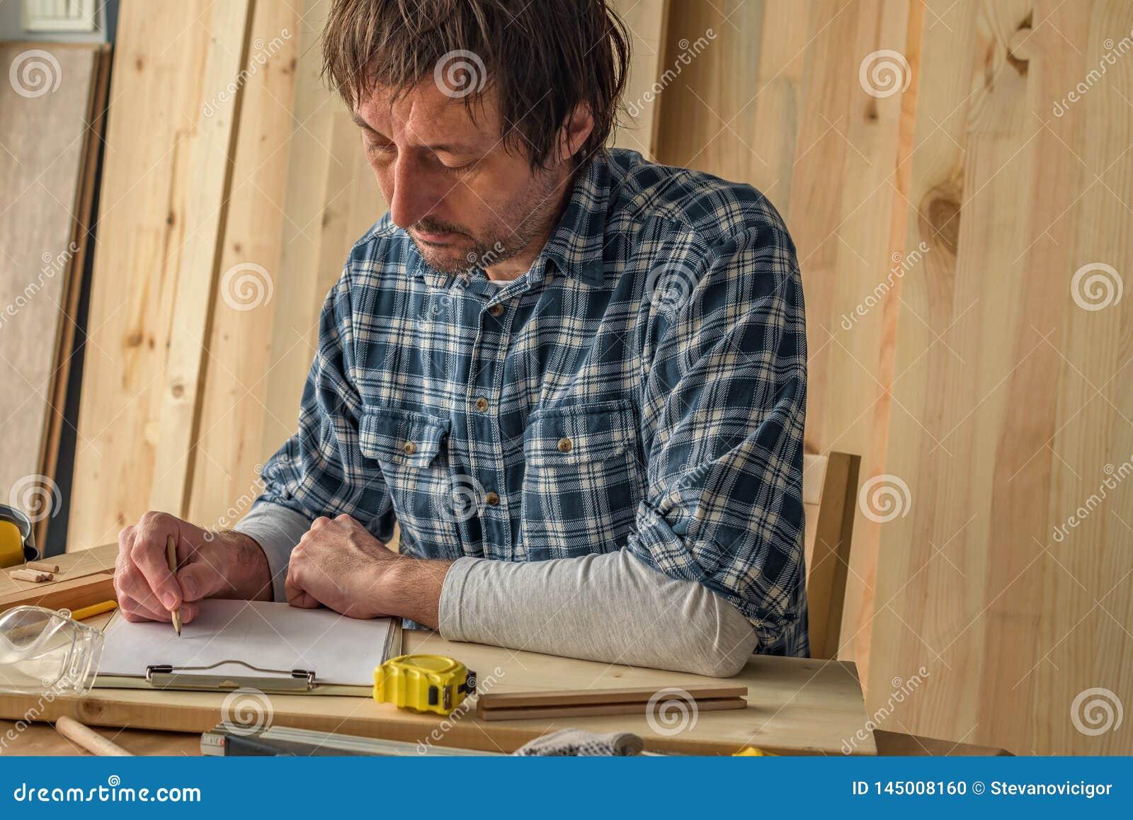 Charpentier faisant des notes de projet de boisage sur le papier de presse-papiers