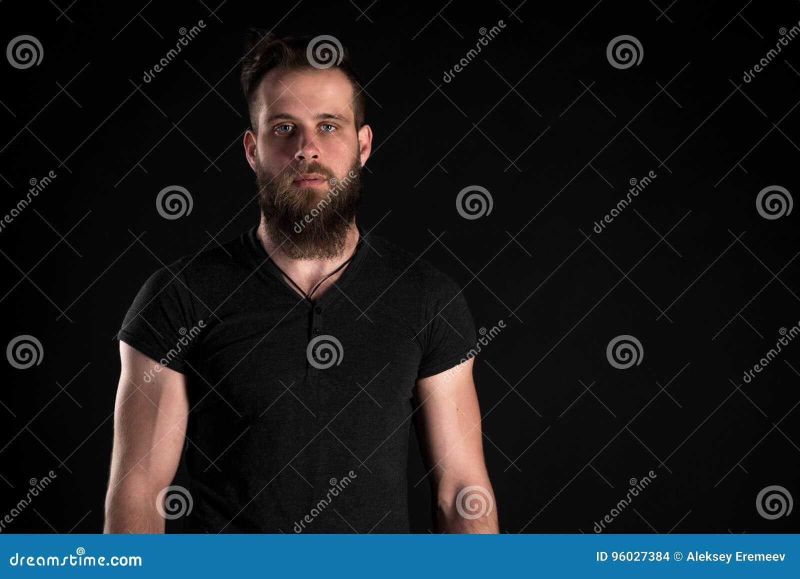 Charyzmatyczny i elegancki mężczyzna z brodą stoi długiego na czarnym odosobnionym tle Horyzontalna rama