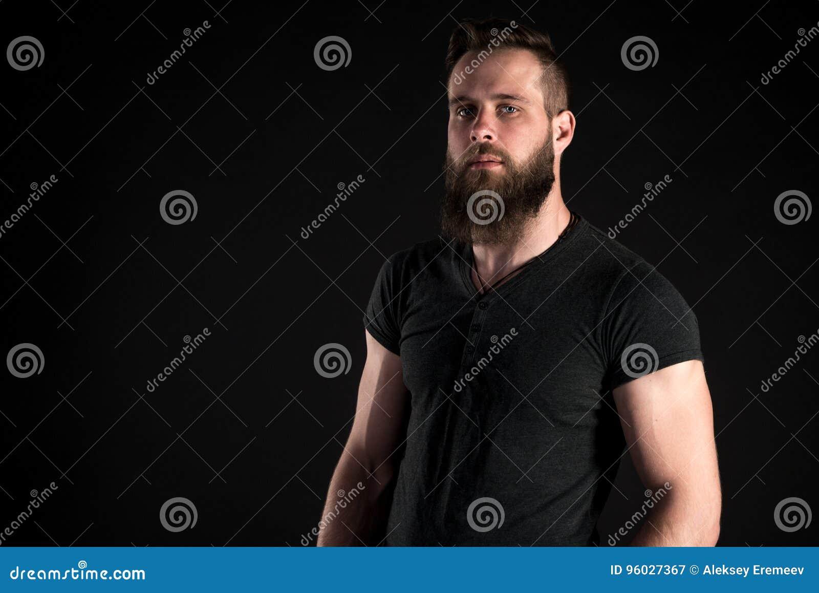 Charyzmatyczny i elegancki mężczyzna z brodą stoi długiego na czarnym tle Horyzontalna rama