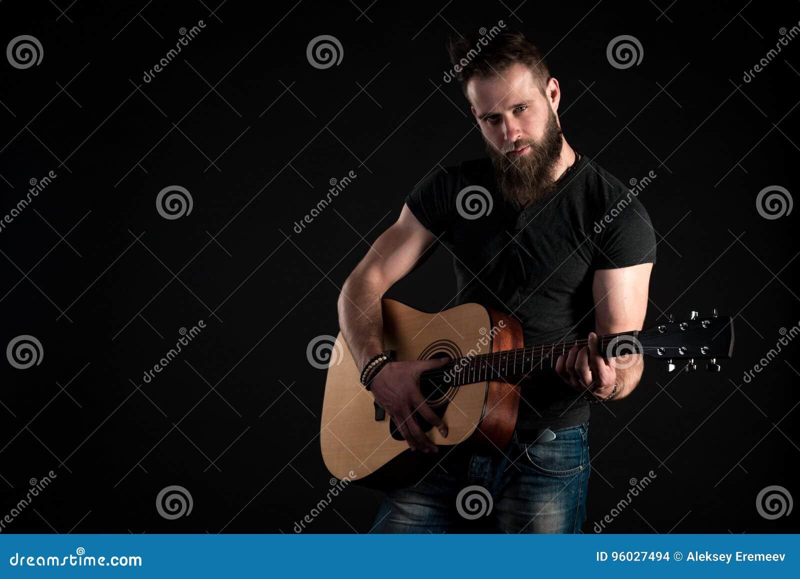 Charyzmatyczny i elegancki mężczyzna z brodą stoi gitarę akustyczną na czarnym odosobnionym tle i bawić się Horyzontalna rama