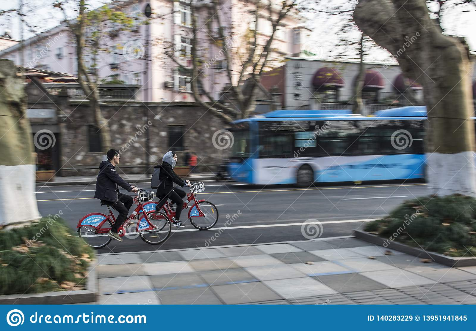 Chasing young men and women riding public bicycles, clear male and female subjects, blurred street background