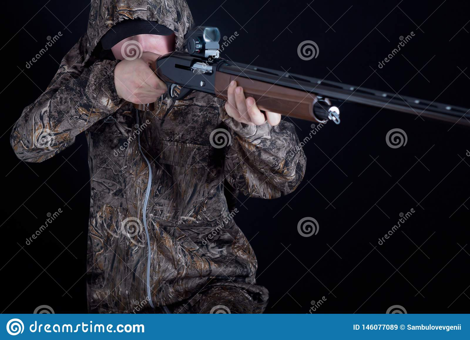 Chasseur dans l habillement de camouflage avec une arme à feu sur un fond noir d isolement L homme avec le fusil de chasse Jeune