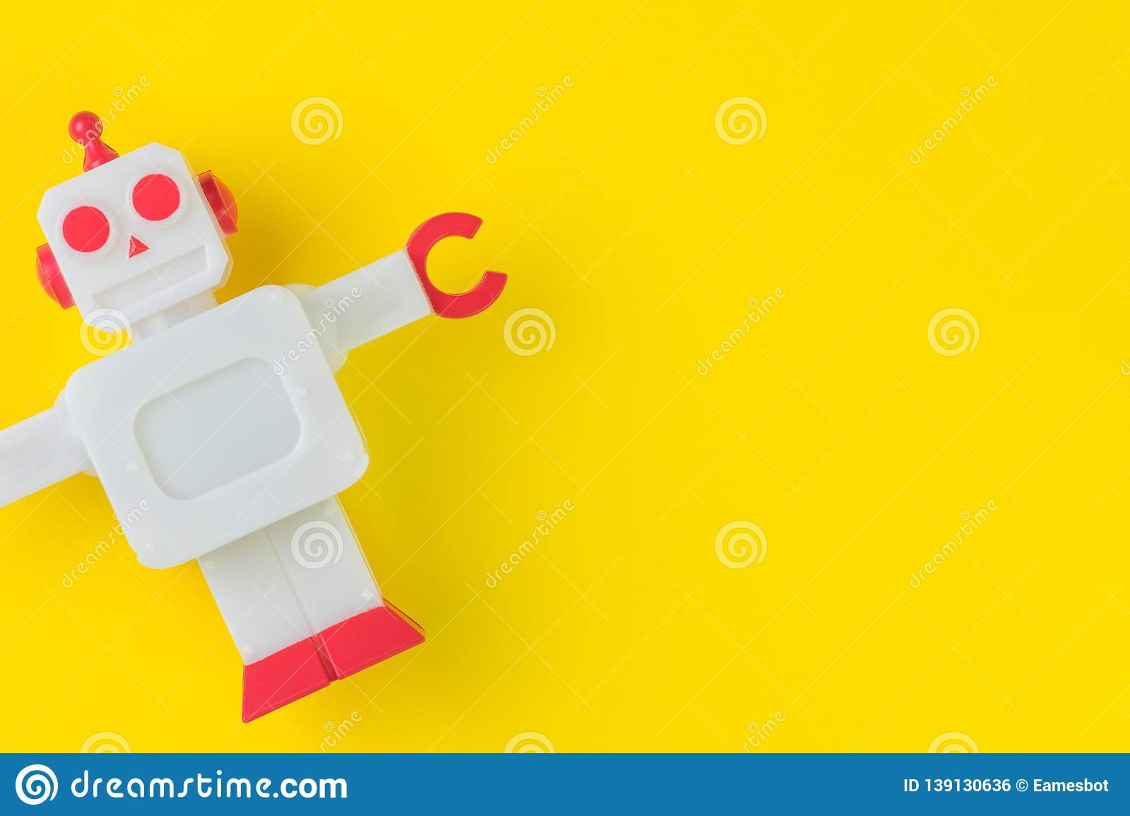 Chatbot or AI Artificial Intelligence or robotic concept, cute vintage look plastic robot on vivid yellow background