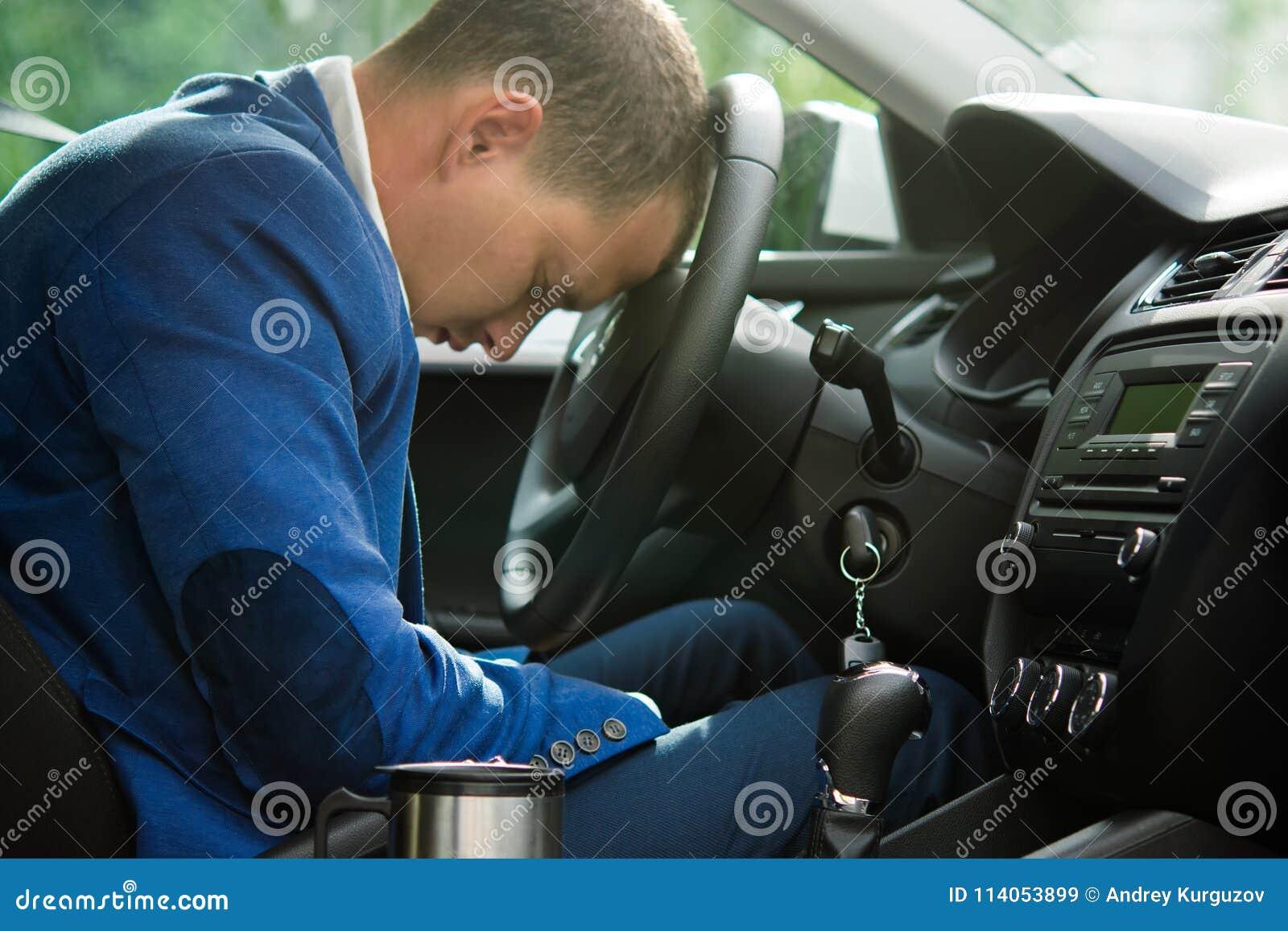 Chauffören avverkar sovande på hjulet av en bil, brist av sömn och trötthet
