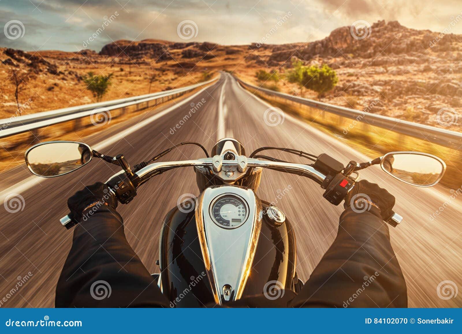 Chaufförridningmotorcykel på asfaltvägen