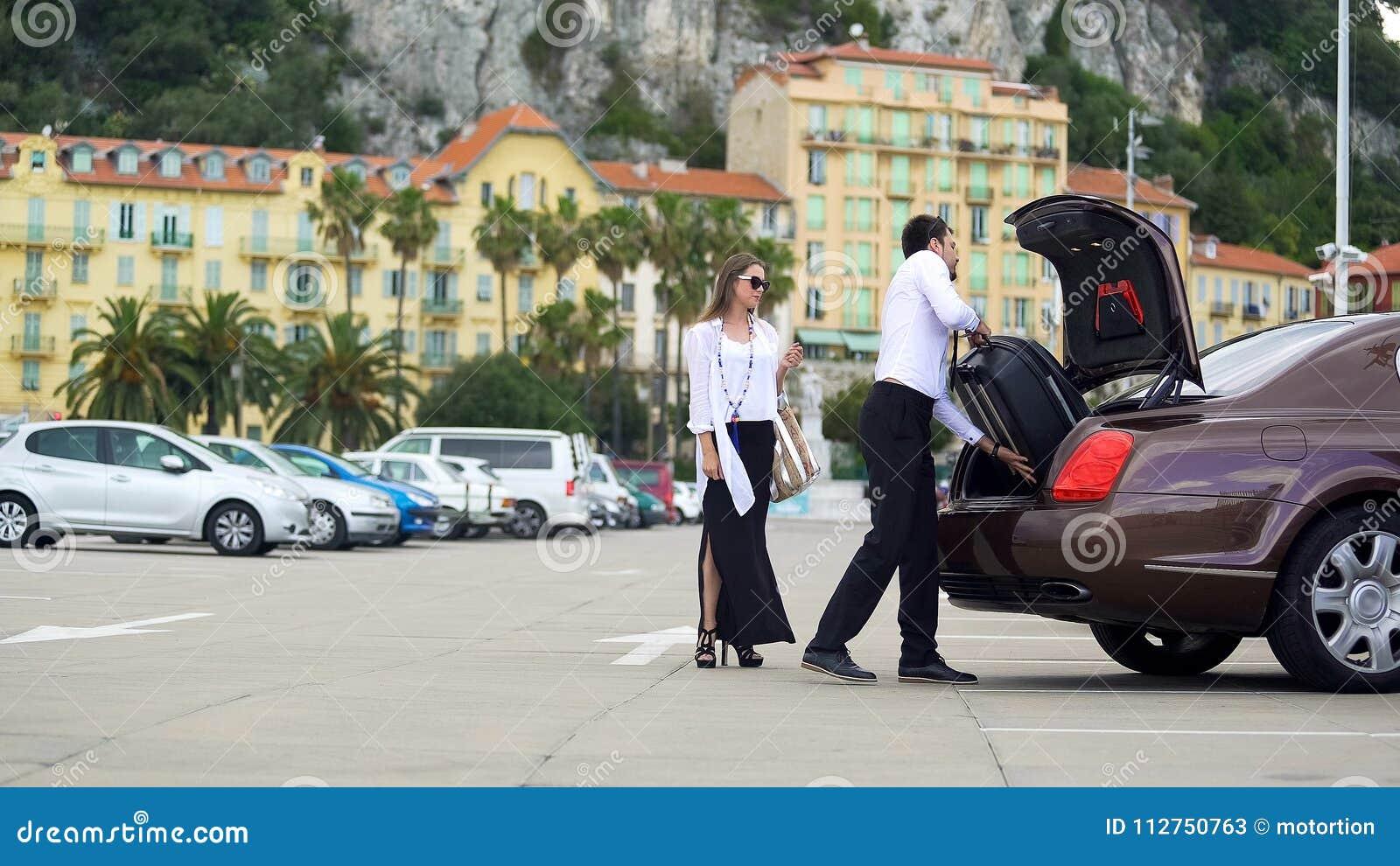 Chauffeur die bagage in boomstam, de dienst van de eliteauto voor bedrijfsmensen zetten