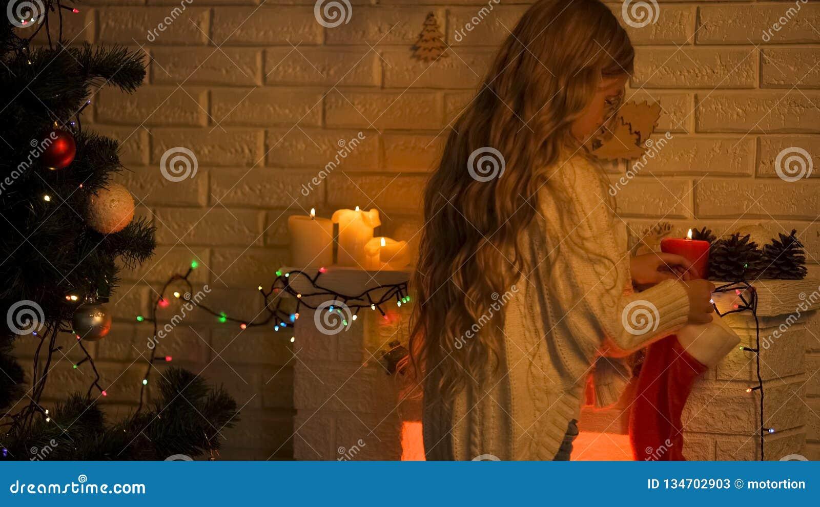 Chaussette accrochante de fille blonde aux cheveux longs sur la cheminée attendant le miracle de Santa Christmas