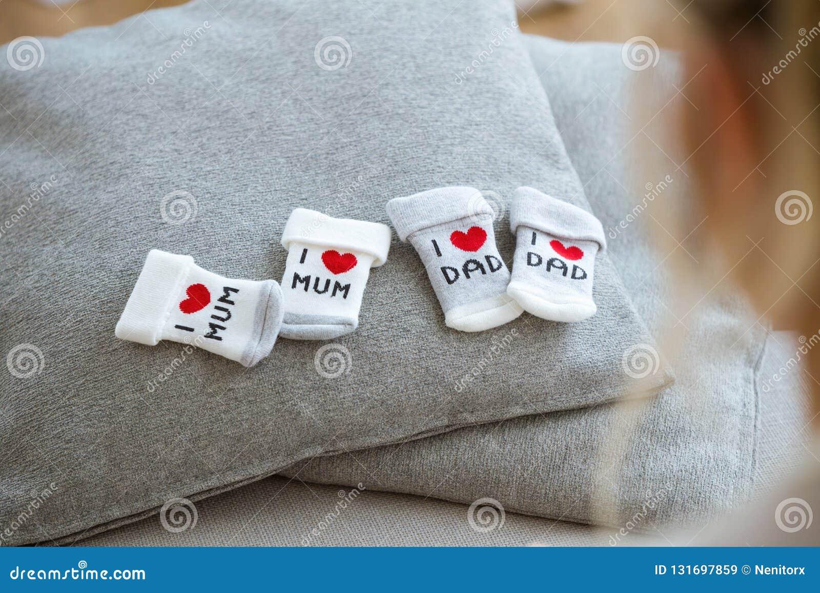 Chaussettes de bébé de coton pour nouveau-né sur un oreiller gris tandis que future mère regardant ils à la maison