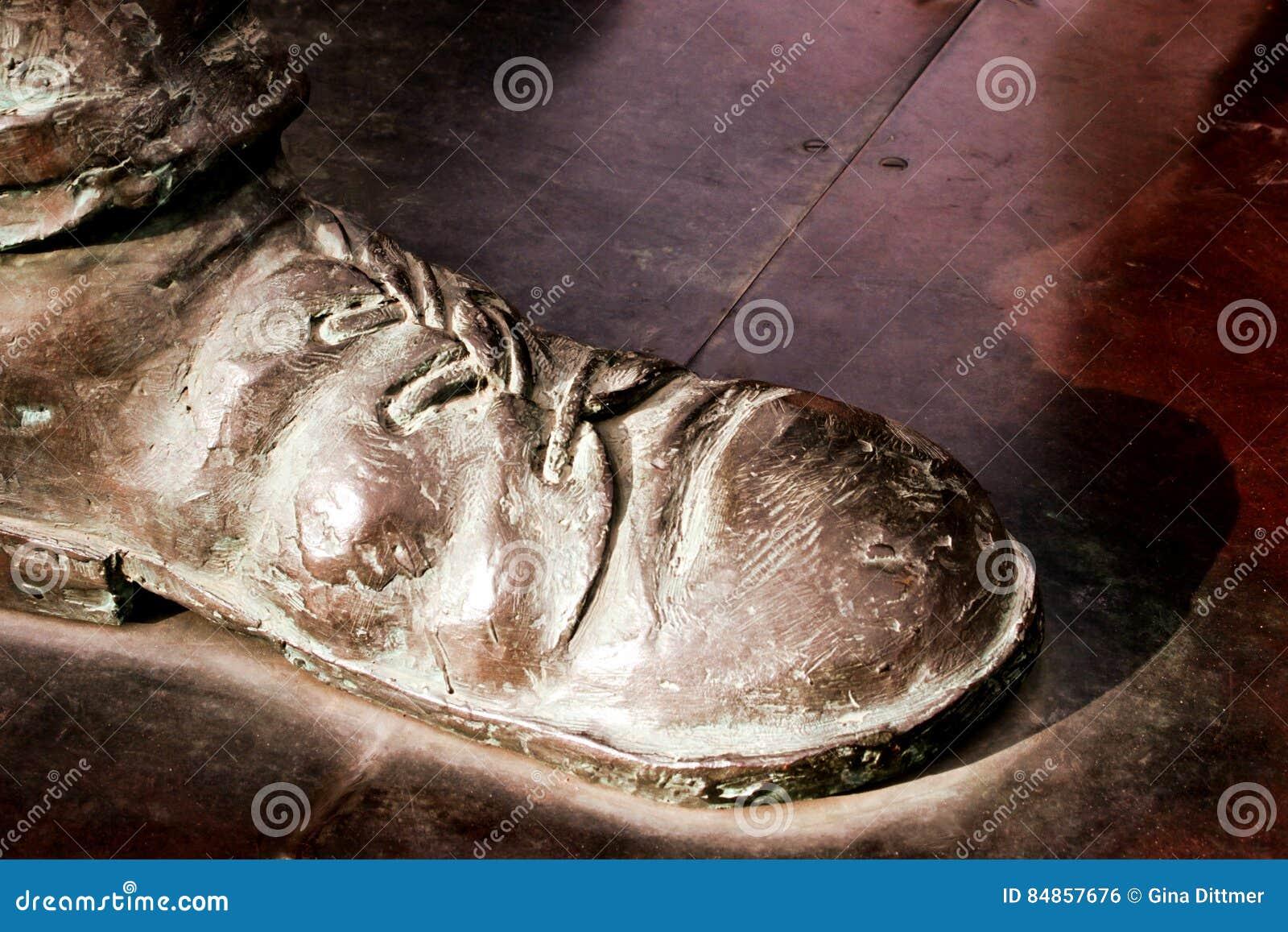 Chaussure en bronze de statue avec des dentelles sur le fond brun-rougeâtre en métal