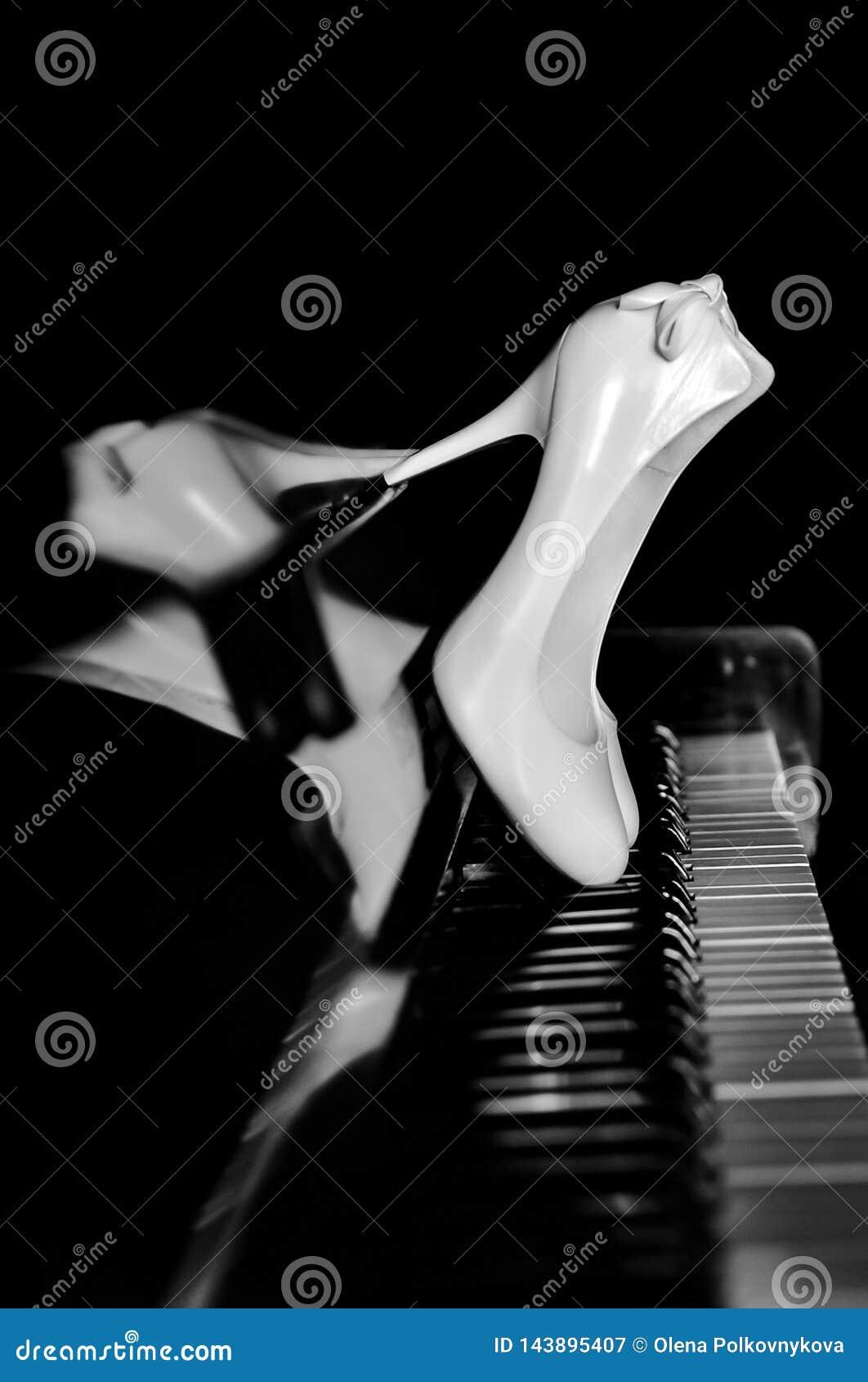 Chaussures blanches de la jeune mariée sur les clés de piano