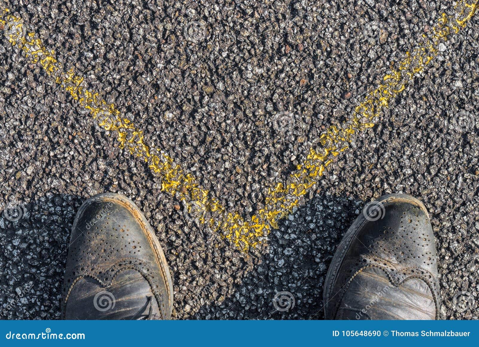 Chaussures d affaires et marque jaune sur l asphalte