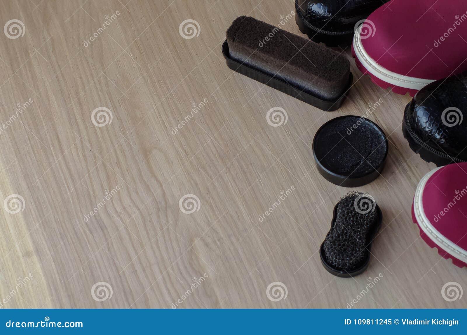 Chaussures et crème de récurage sur le plancher Nettoyez les chaussures pour la marche