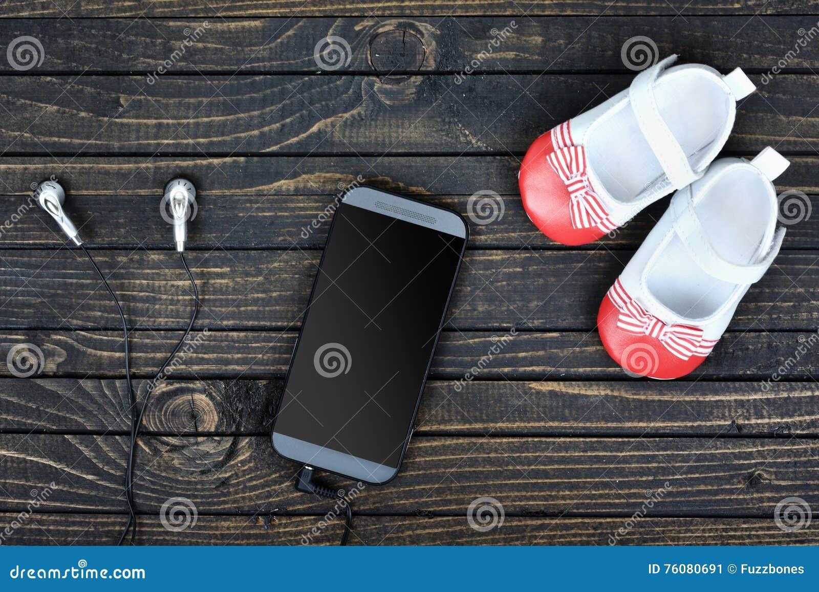 Chaussures et téléphone d enfant sur le plancher