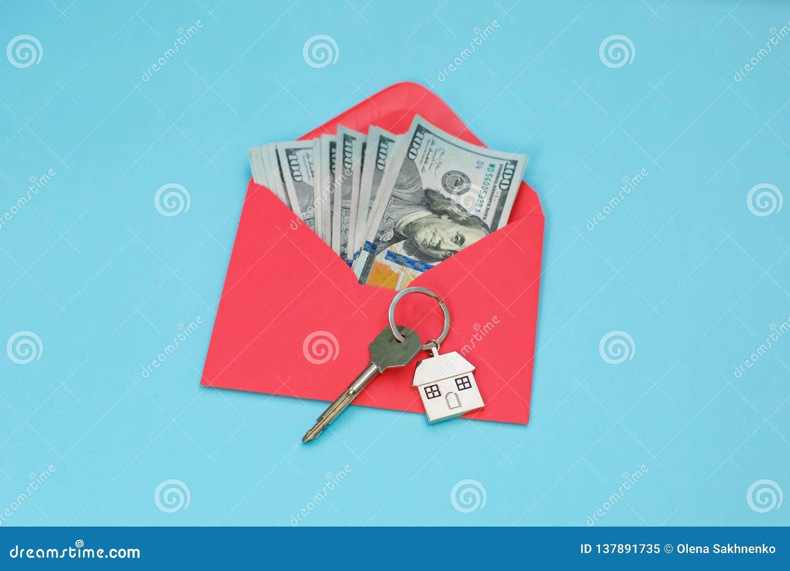 Chaves da casa sobre as cédulas do dólar americano no envelope vermelho