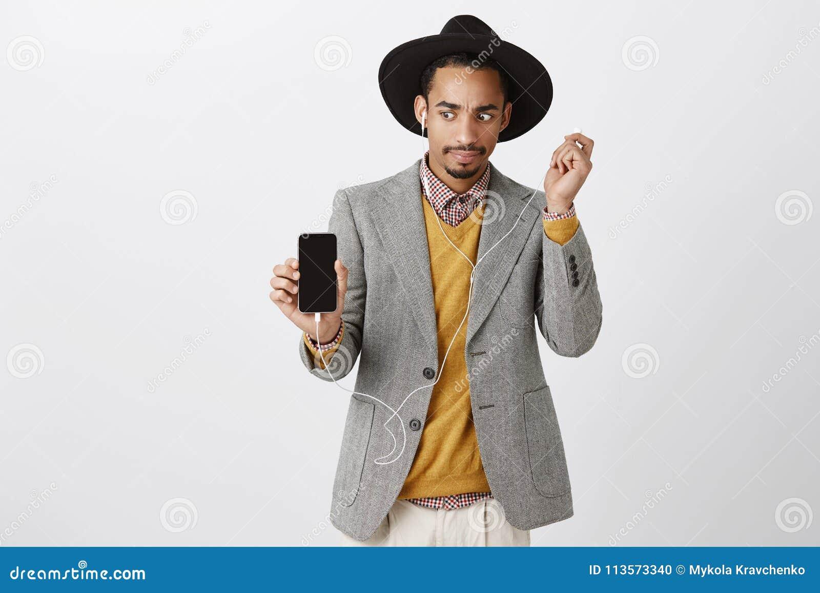 Che cosa è sbagliato con il suono Surprised ha preoccupato il tipo bello in vestiti e cappello d avanguardia, mostrando lo smartp