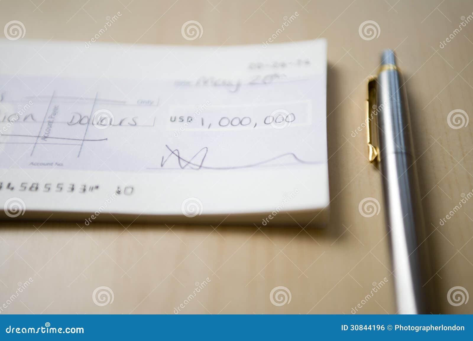 Check för en miljon dollar som ligger bredvid penna på tabellnärbild