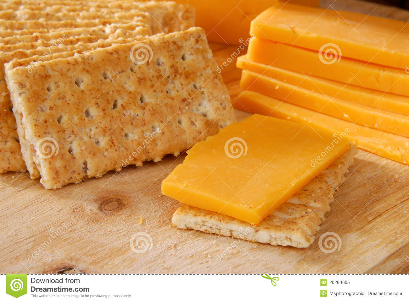 ... cheese and crackers on a cutting board - focus on front cracker