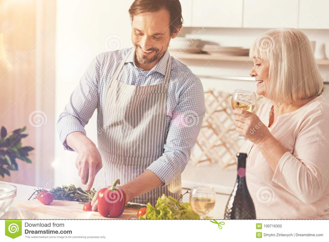 Cook with love. Cheerful smiling adult men wearing apron and cooking  vegetable salad while his aged mother drinking white wine