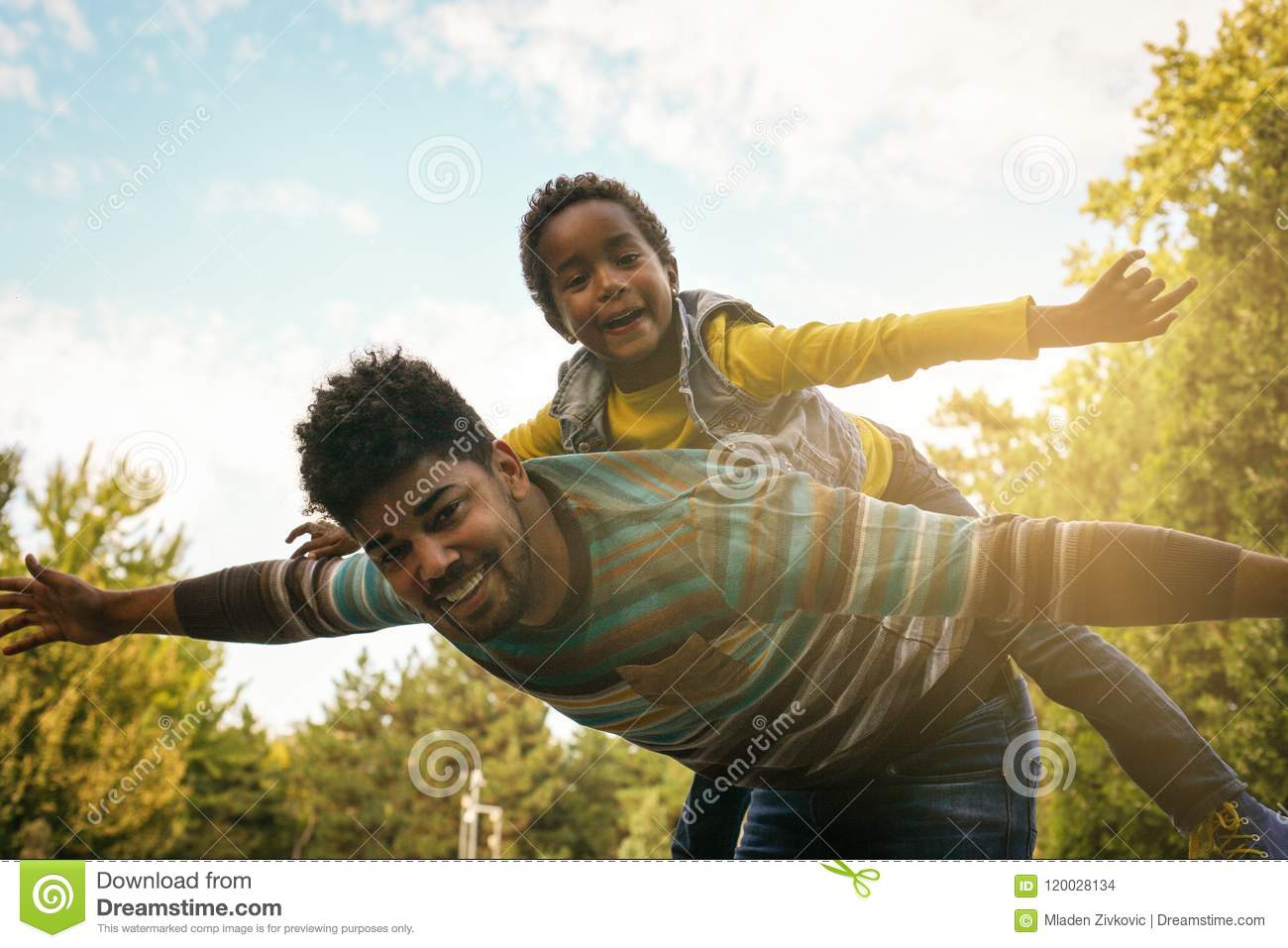 African American father holding her daughter on shoulde