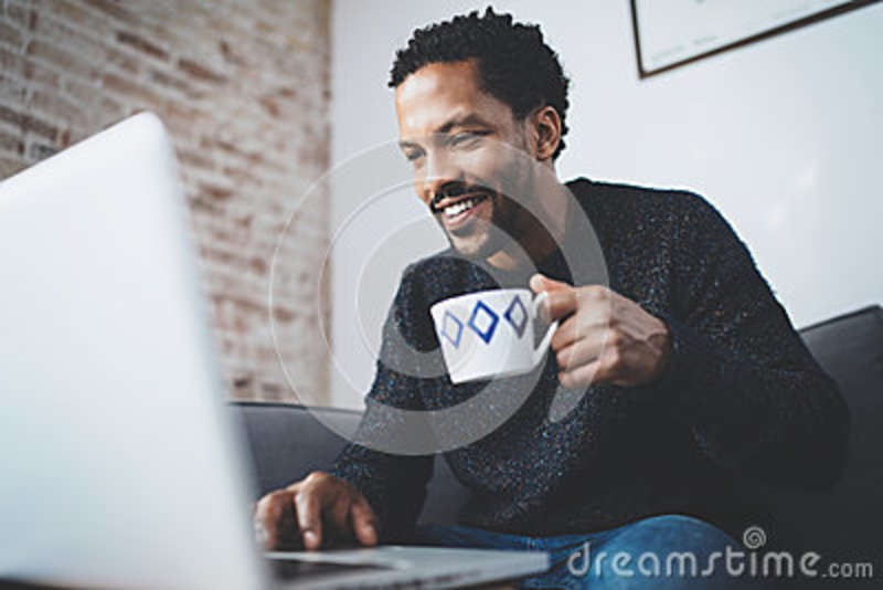 Cheerful African man using computer and smiling while sitting on the sofa.Black guy holding ceramic cup in hand.Concept