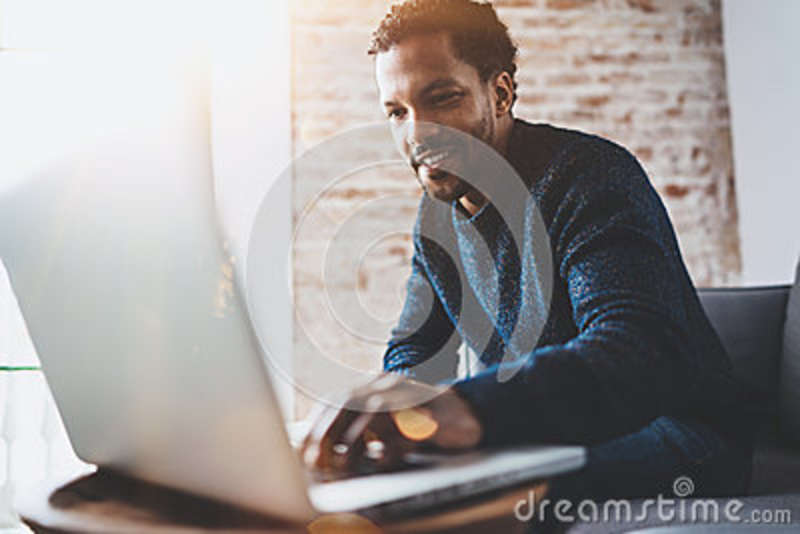 Cheerful African man using computer and smiling while sitting on the sofa.Concept of young business people working at