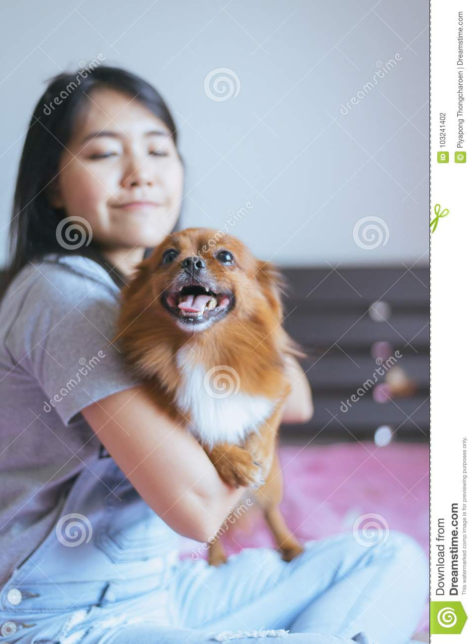Cheerful asian young teen girl playing and happy fun with her dog at home