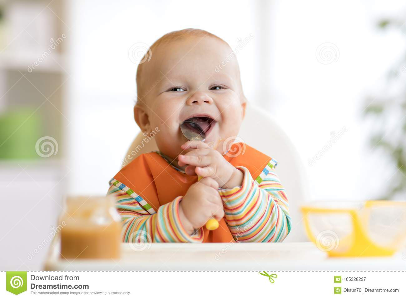Cheerful baby child eats food itself with spoon. Portrait of happy kid boy in high-chair.