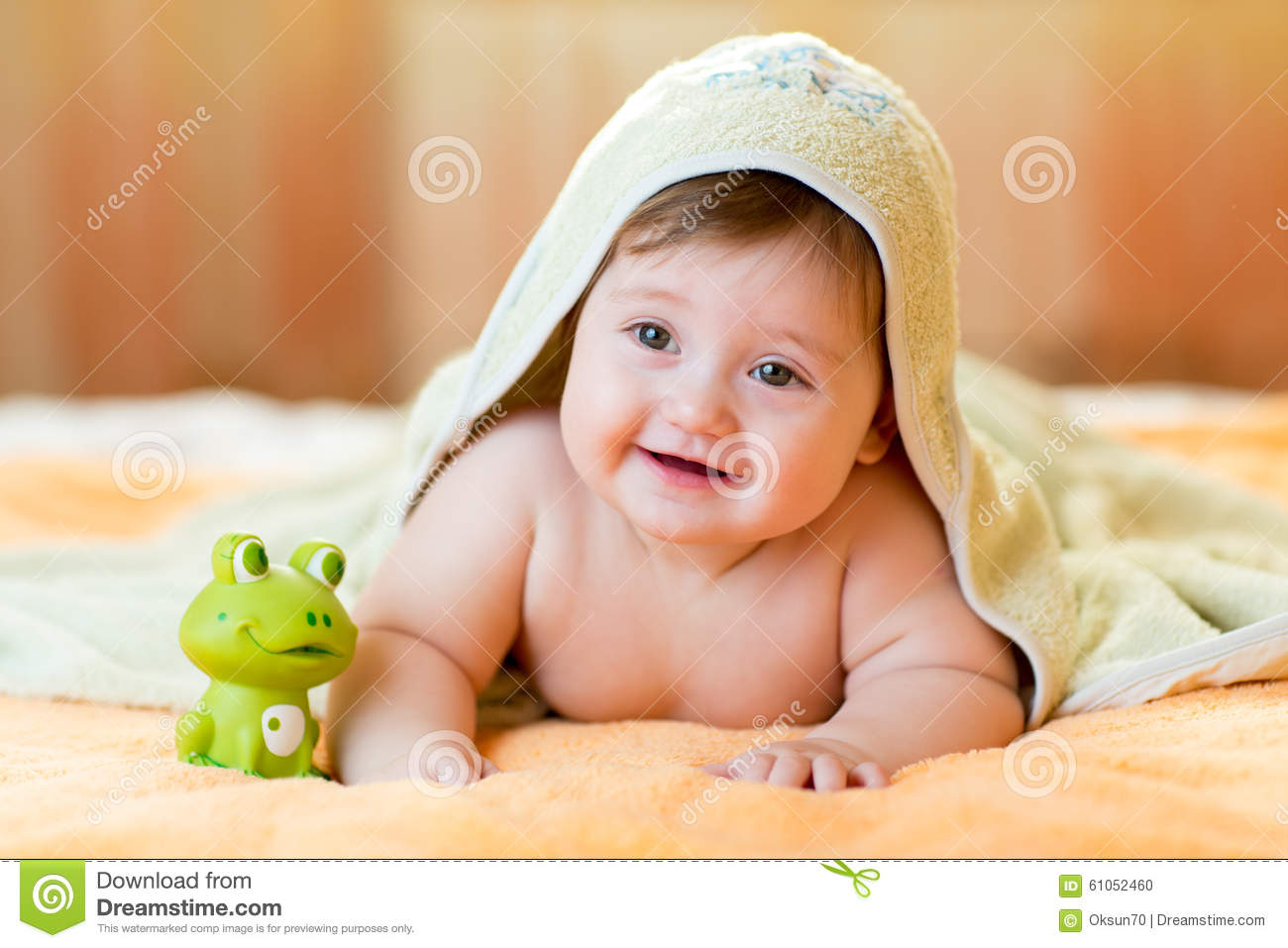 Cheerful baby child under a hooded towel after