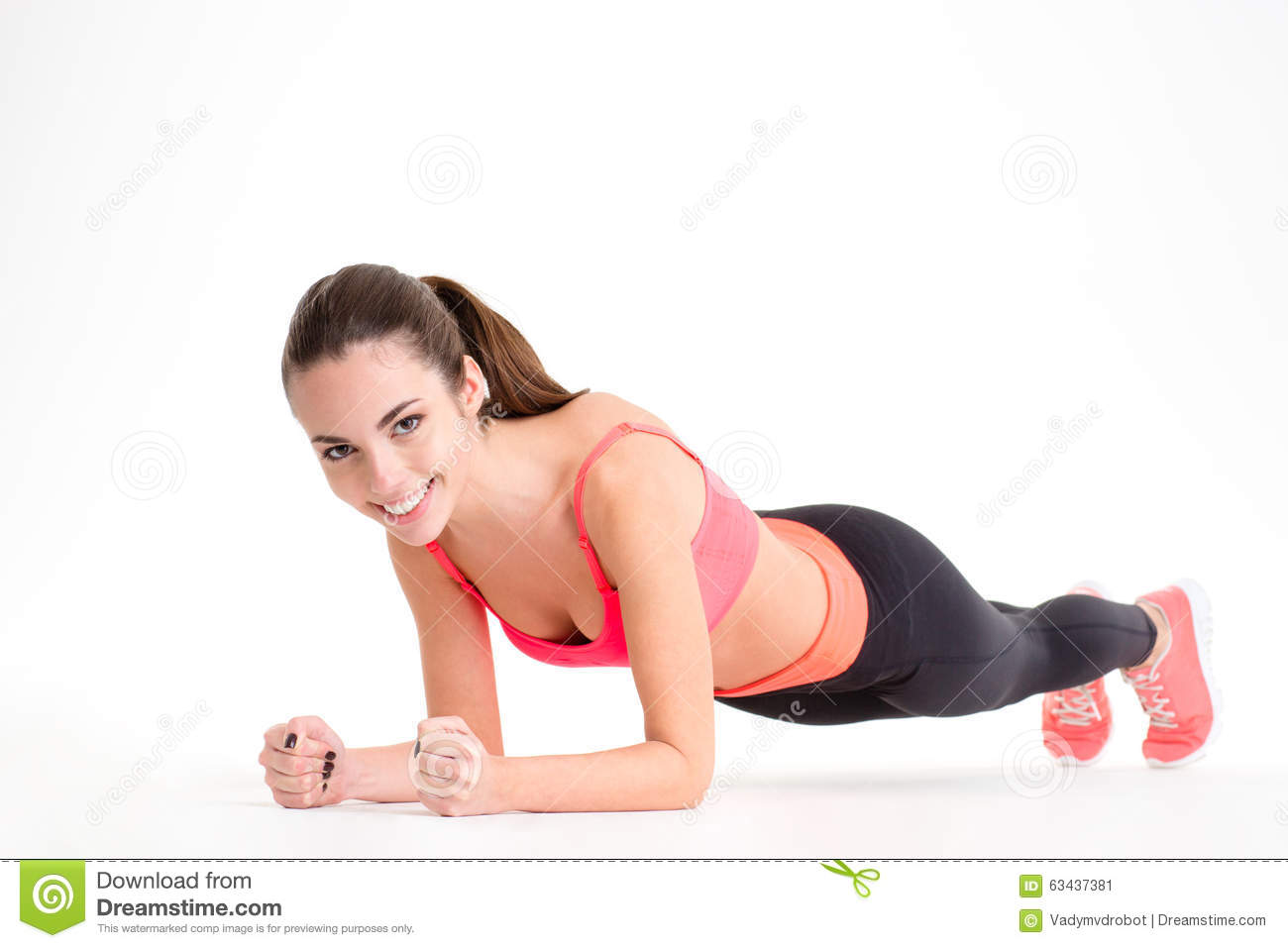 Cheerful beautiful fitness woman doing plank exercise