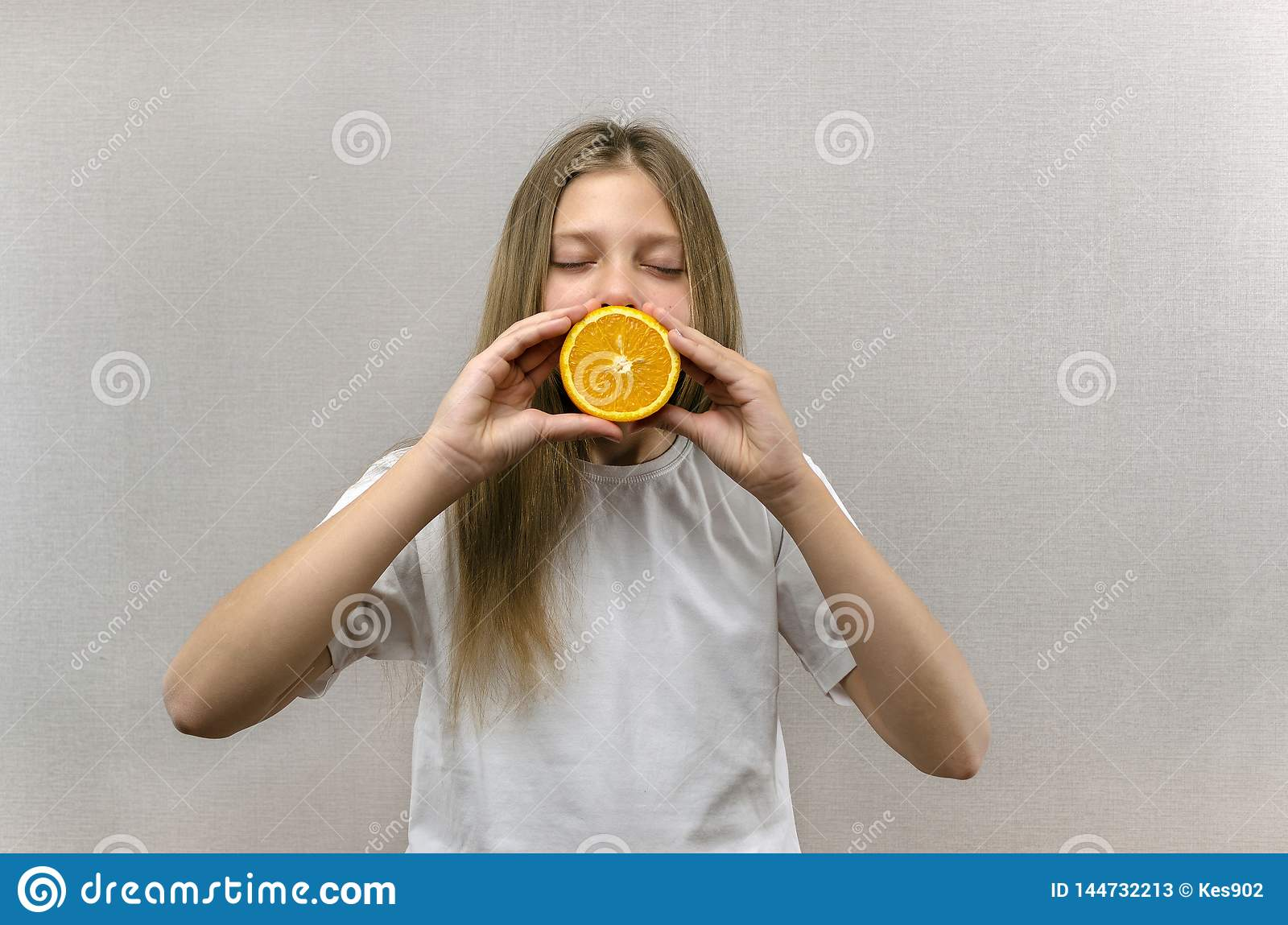 Cheerful beautiful girl holds in halves of orange halves. Positive emotions. Healthy food. Veggie and Vegan