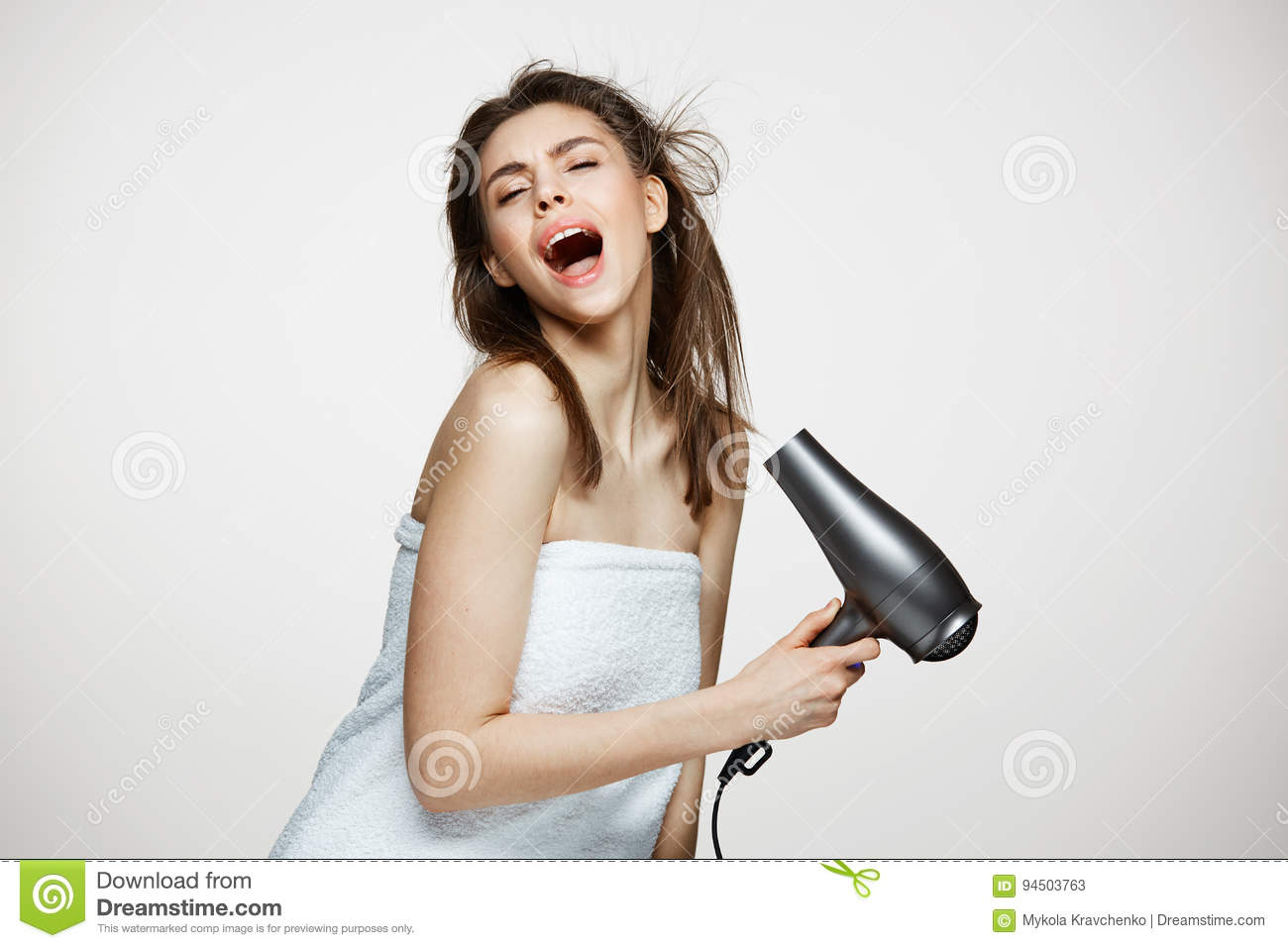 Cheerful beautiful girl in towel smiling laughing singing with hair dryer making funny face over white background