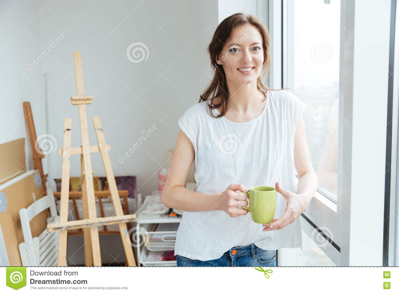 Pretty cheerful young woman painter painting in art studio for Painting studios near me