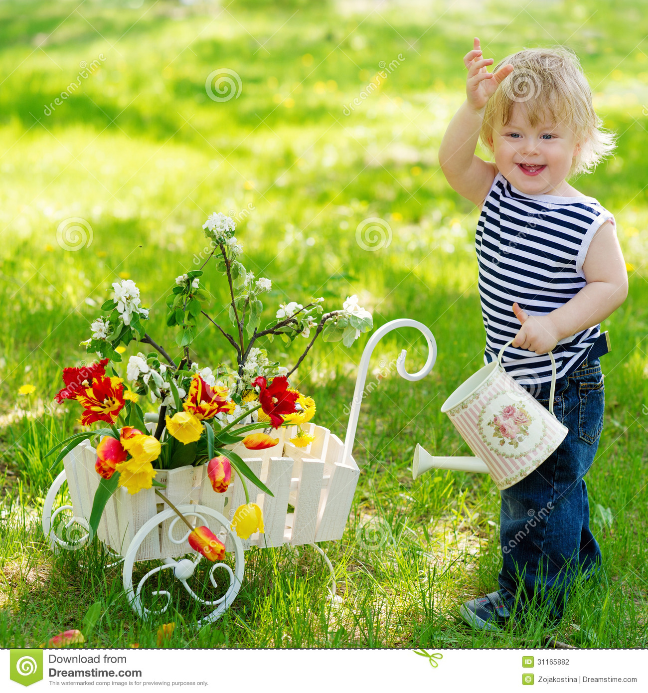 cheerful boy with watering can and flowers
