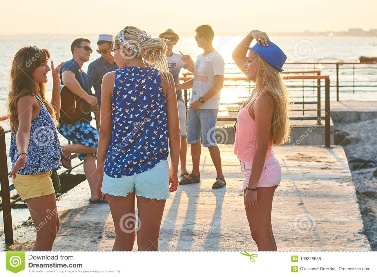 Cheerful and carefree group of friends hanging out at the sunny summer seaside on their vacation