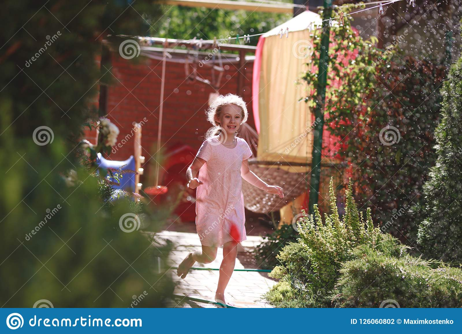 A cheerful charming seven-year-old girl enjoys a sunny summer morning and has fun in the garden at home