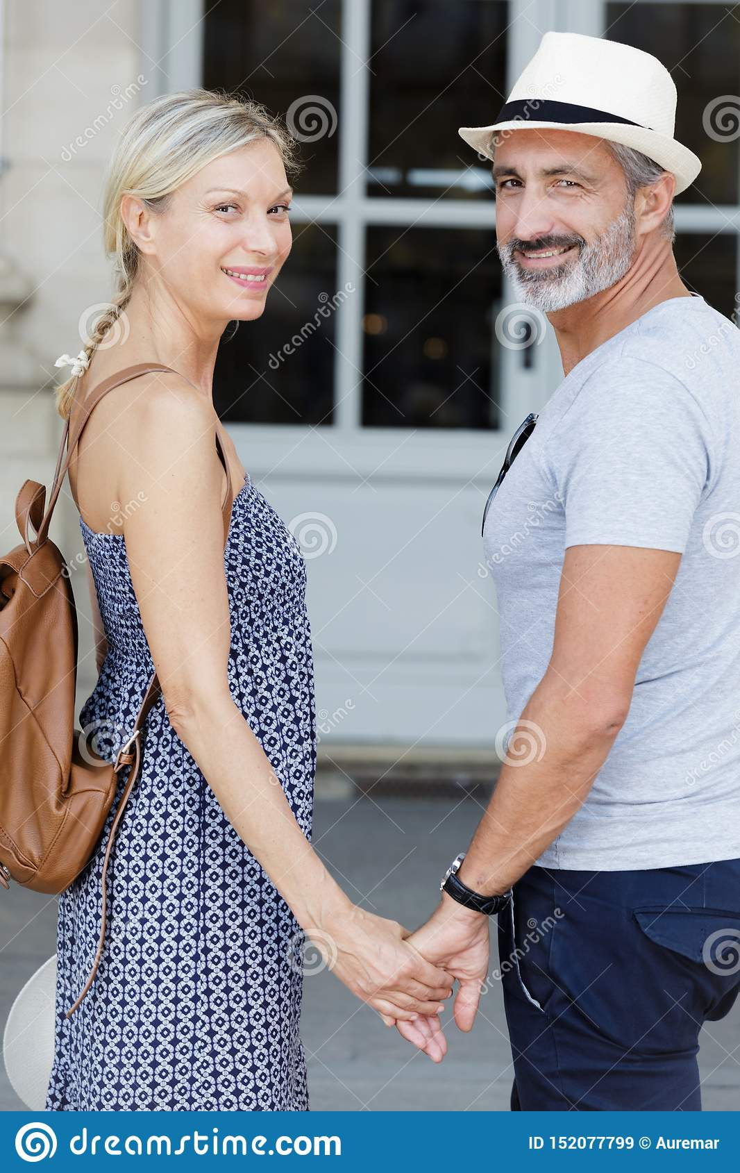 Cheerful couple holding hands outdoors