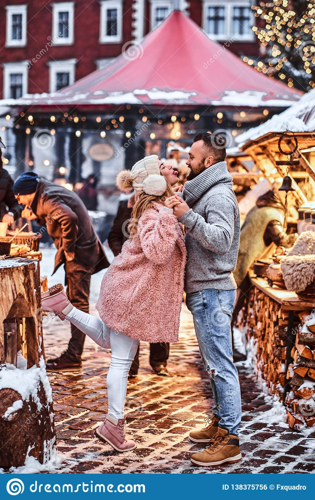 An attractive couple in love, having fun together at a Christmas fair.