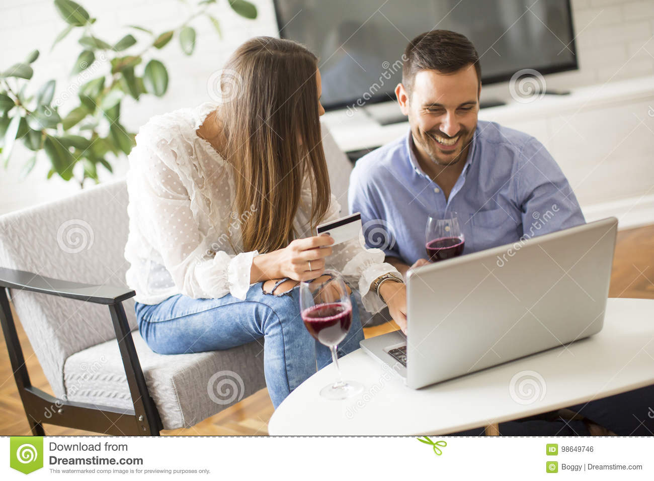 Cheerful couple searching internet and shopping online