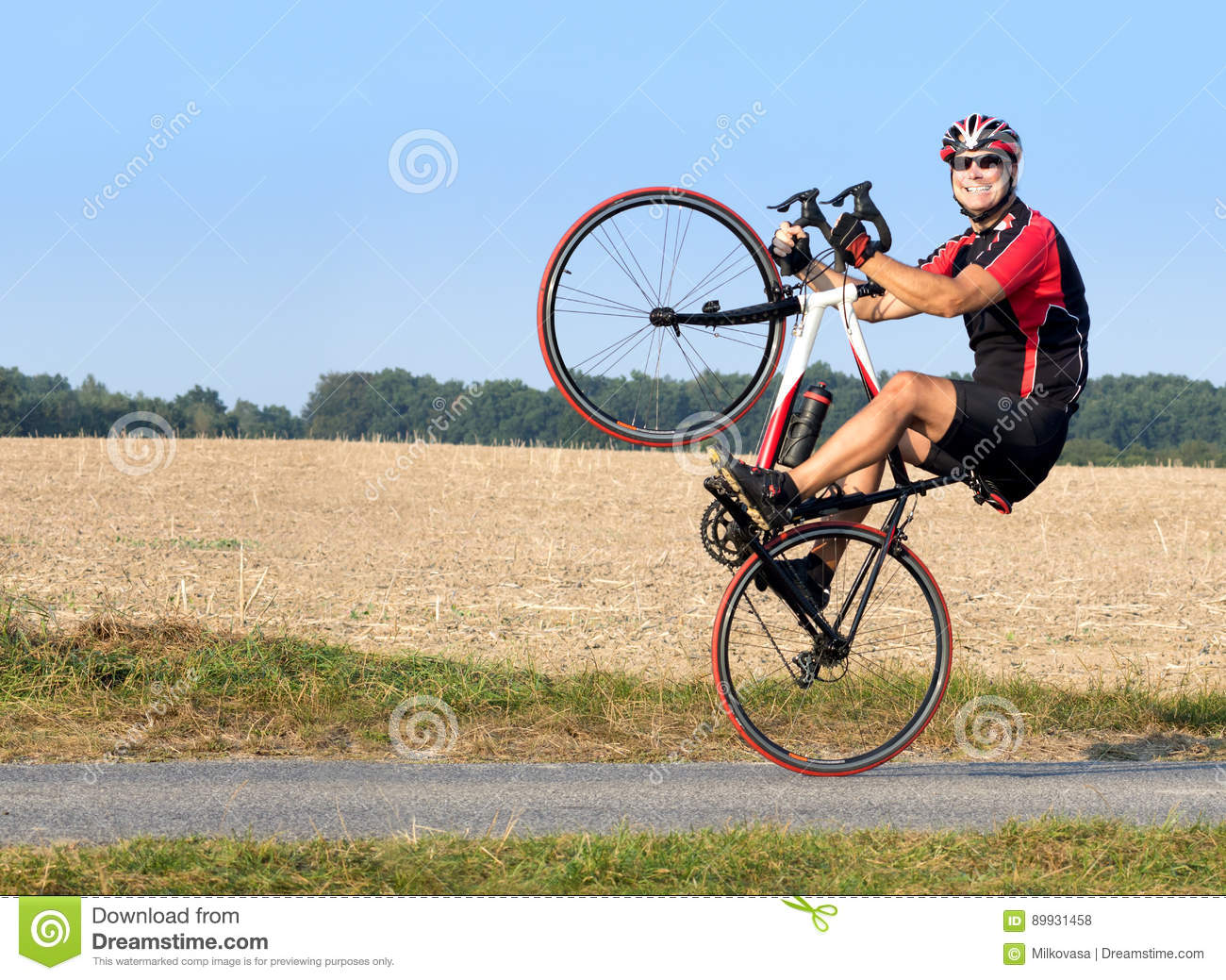 9456a2a8fd5 Cheerful Cyclist Riding On The Rear Wheel. Stock Photo - Image of ...