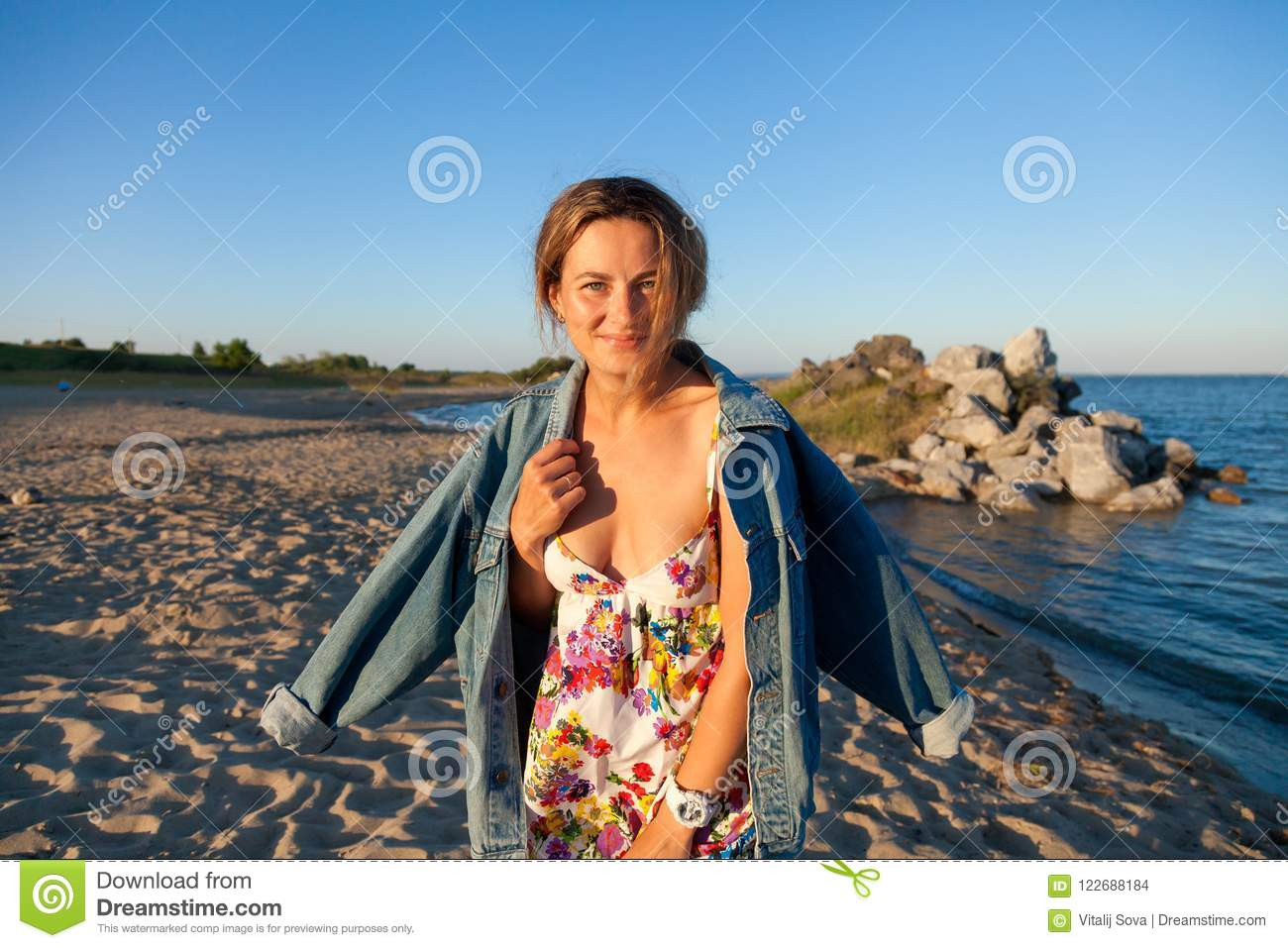 A cheerful dark-haired woman in the colored thread and denim jacket smiles, walks along the beach and enjoys the bright sun on a