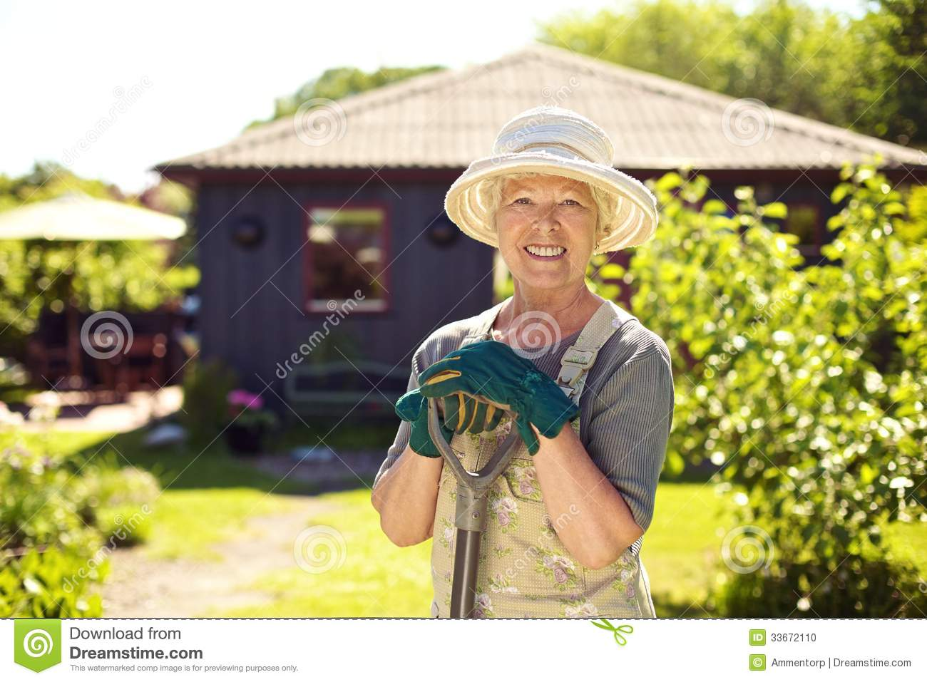 Cheerful elder woman with gardening tool in backyard stock for Gardening tools for seniors