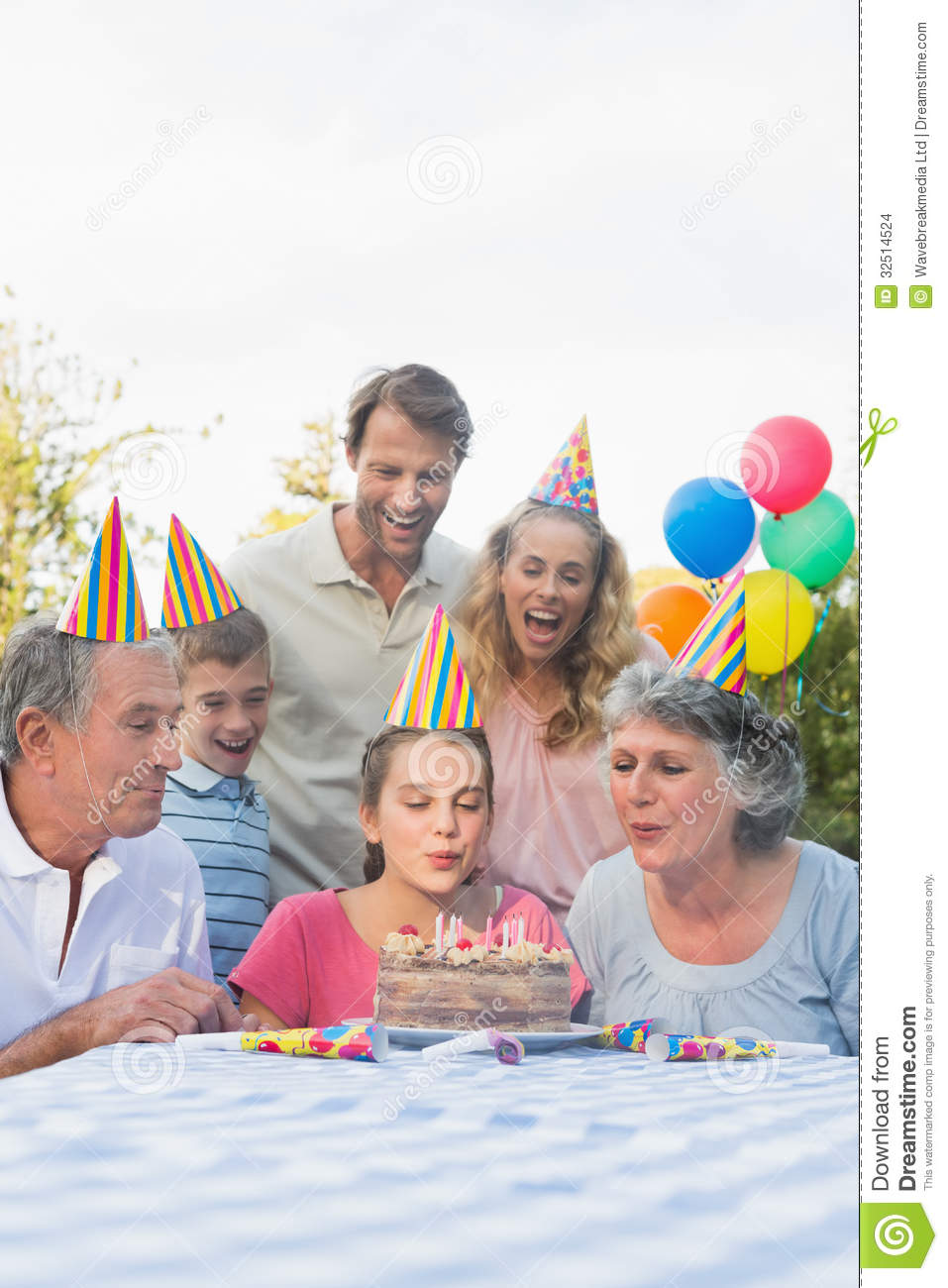 Cheerful Extended Family Blowing Out Birthday Candles ...