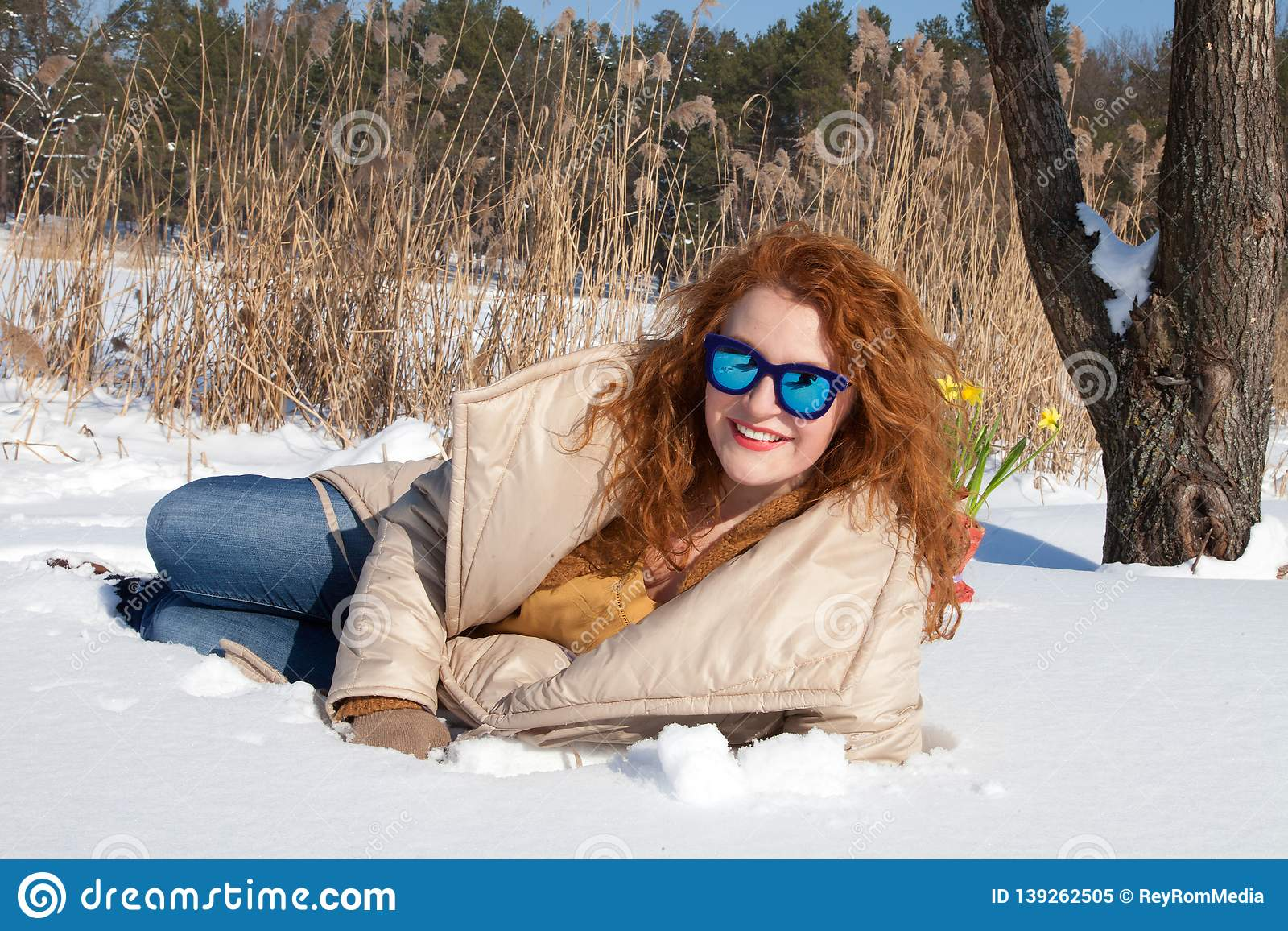 Cheerful fashionable woman resting in snow against rural environment