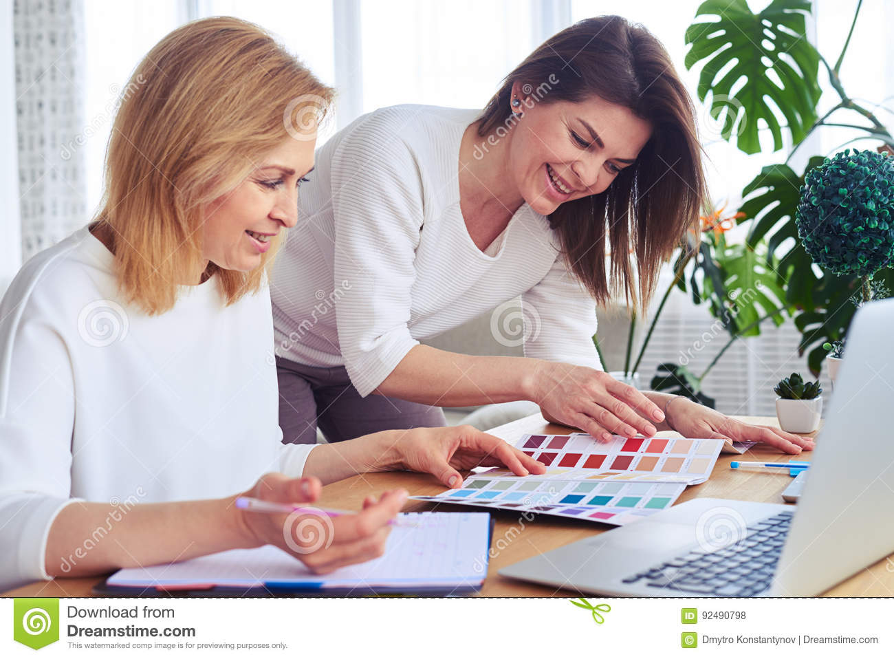 Cheerful females working with catalog of color palette