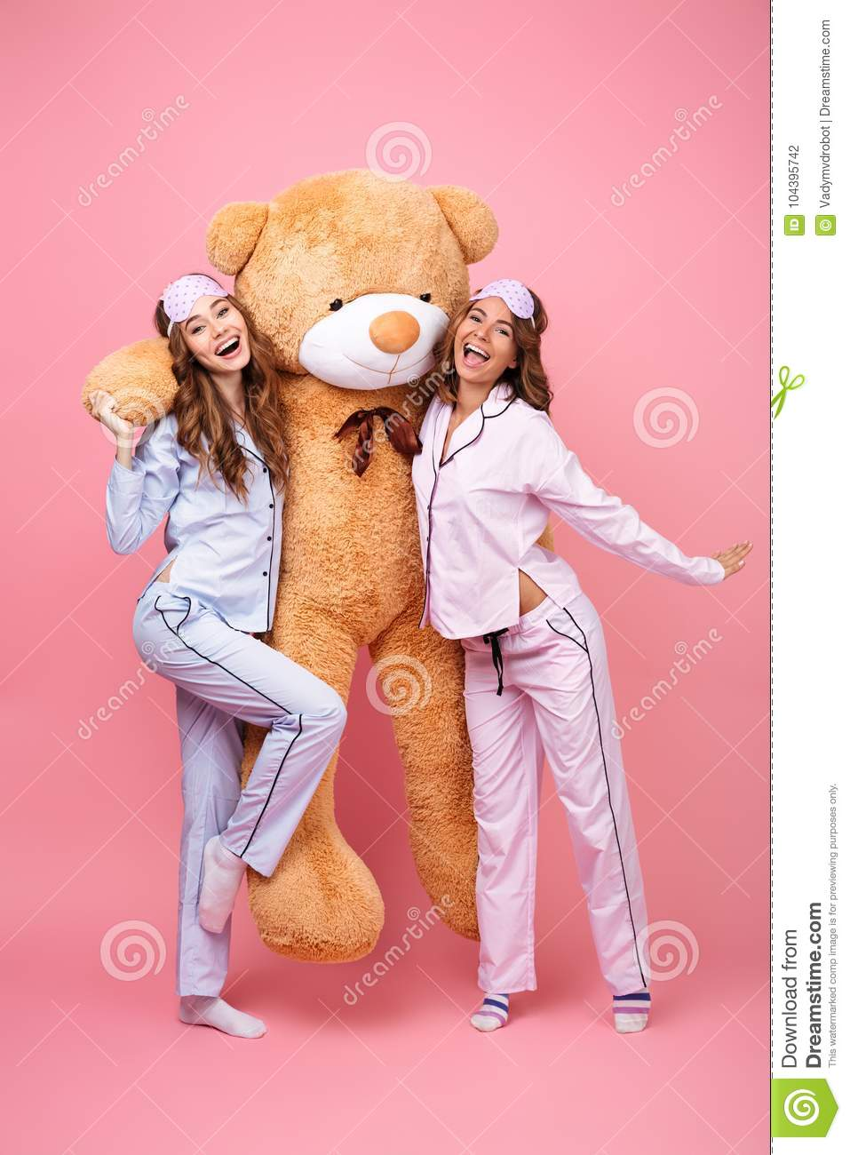 Picture of two cheerful friends women in pajamas isolated over pink  background hug big teddy toy bear. Looking camera. ee7053024