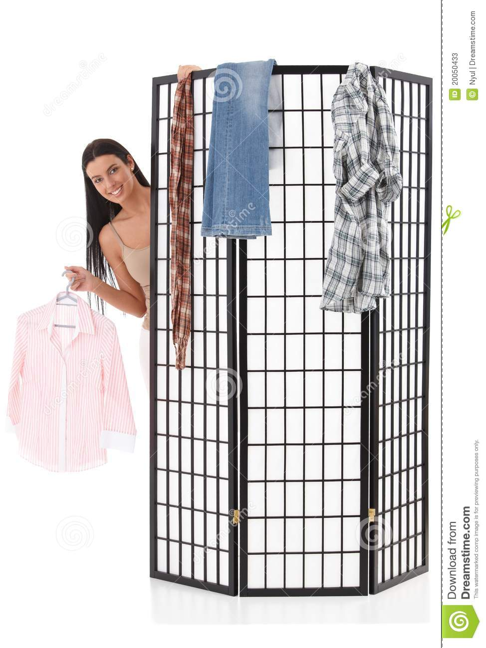 Cheerful girl dressing up behind dressing panel