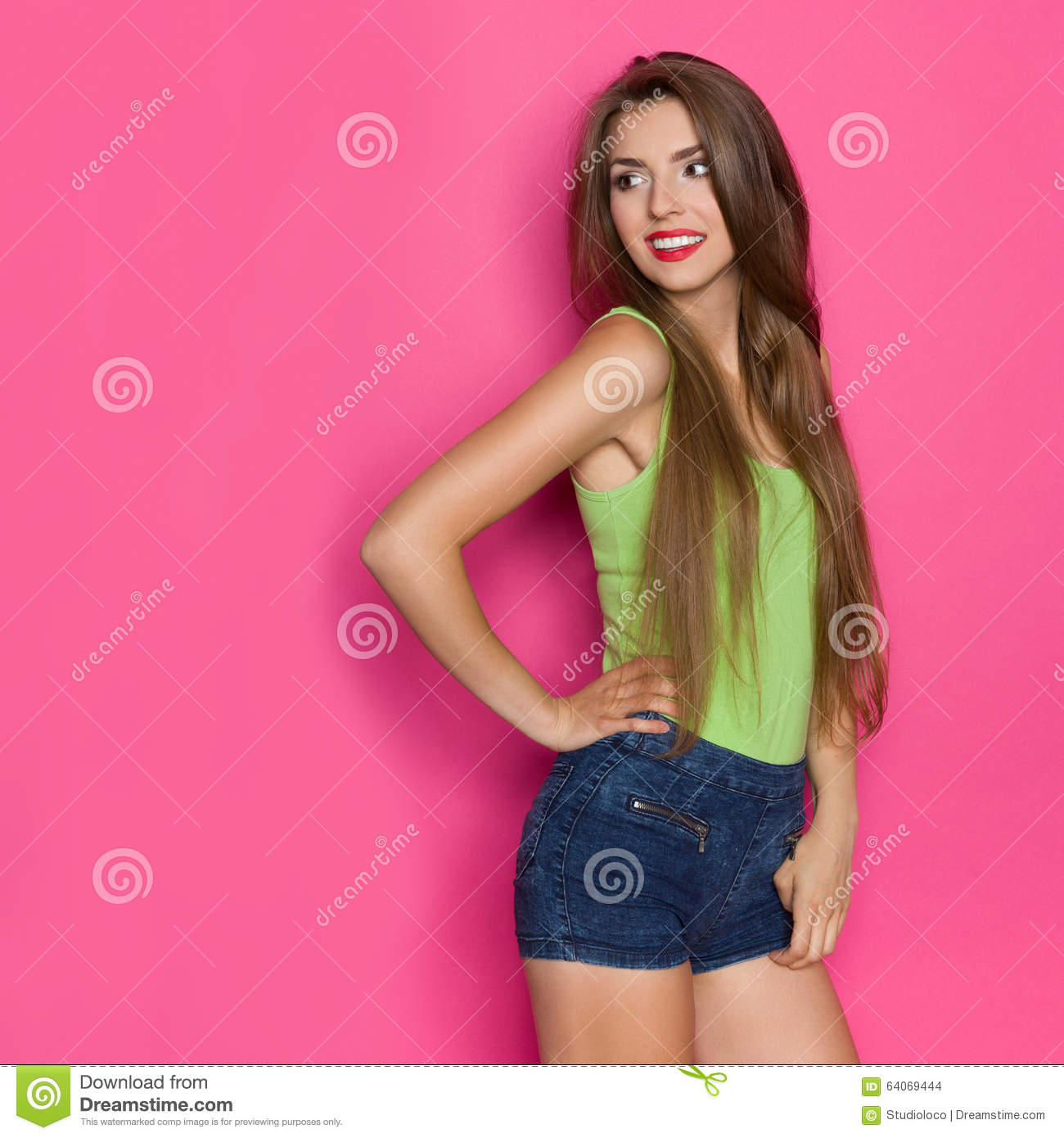 18cda52a137972 Young beautiful woman in jeans shorts and lime green shirt posing with hand  on hip and looking away at copy space. Three quarter length studio shot on  pink ...