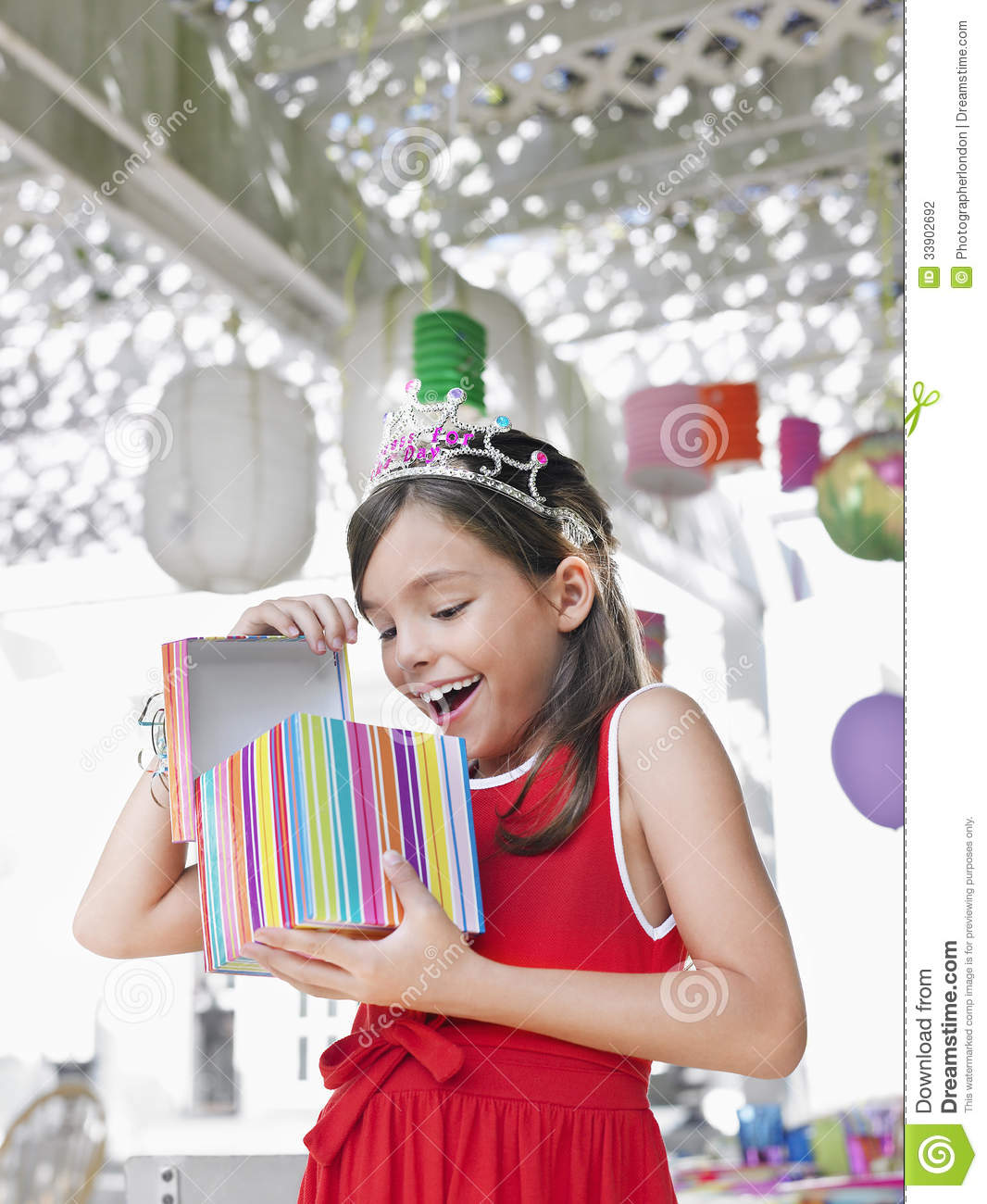 Cheerful Girl Opening Birthday Present At Party Stock