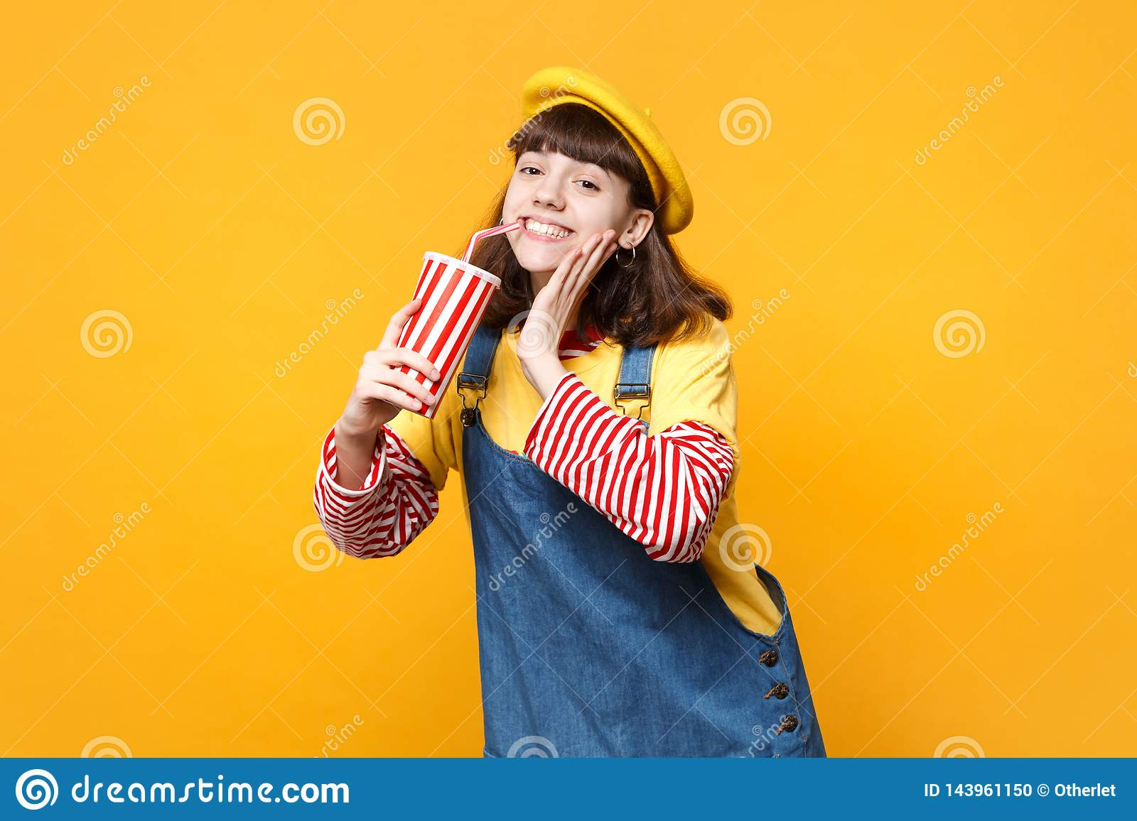 Cheerful girl teenager in french beret, denim sundress hold plastic cup of cola or soda put hand on cheek isolated on