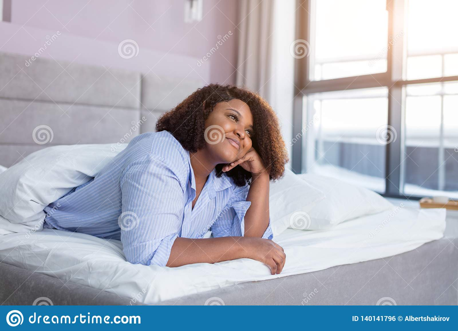 Cheerful girl thinking about her boyfriend while resting in the comfortable bed